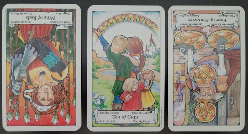 Three cards lay on a black surface. From left to right is the Nine of Rods Reversed, the Ten of Cups, and the Four of Pentacles Reversed. image